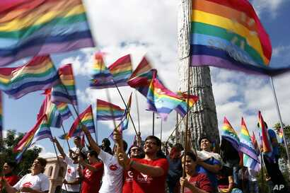 Gays and lesbians wave gay pride flags before a Kiss-A-Thon against homophobia in Asuncion, Paraguay, May 17, 2016.