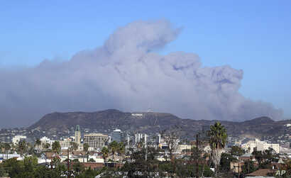 Smoke from the Creek wildfire in the San Gabriel Mountains, the second range behind the Hollywood Hills, home of the Hollywood sign, looms up over Los Angeles Tuesday morning, Dec. 5, 2017.