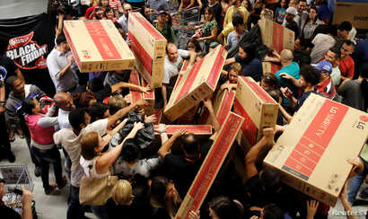 Shoppers reach for television sets as they compete to purchase retail items on Black Friday at a store in Sao Paulo, Brazil, Nov. 24, 2016.