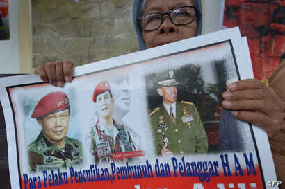 "FILE - An Indonesian protester holds a placard featuring Prabowo Subianto, center, reads, ""Doers kidnapping, killing and human rights violators"" during a protest against presidential candidate Prabowo Subianto in Jakarta, Indonesia, May 20, 2014. For..."