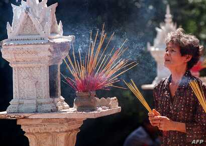 A Cambodian woman burns incense as she prays for good fortune and health in front of a small prayer house at Wat Phnom Pagoda, Phnom Penh, Jan. 31, 1999.