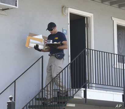 A federal agent removes items from an apartment following the arrest of a 45-year-old Iraqi refugee, Omar Ameen, Wednesday, Aug. 15, 2018, in Sacramento, Calif.