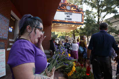 Cynthia Sullivan of Charlottesville, Va., stands in line for a memorial service for Heather Heyer, who was killed during a white nationalist rally, in Charlottesville, Va., Aug. 16, 2017.