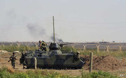 FILE - This Oct. 5, 2012, photo, Turkish military take up positions on the Turkish side of the Syrian border