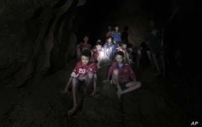 This Monday, July 2, 2018, photo released by Tham Luang Rescue Operation Center, shows the boys and their soccer coach as they were found in a partially flooded cave, in Mae Sai, Chiang Rai, Thailand