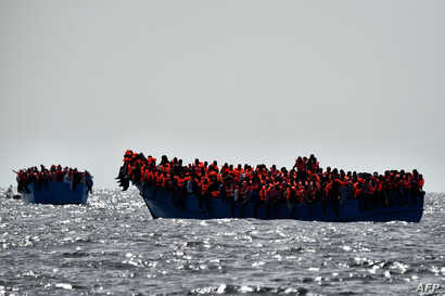 Migrants wait to be rescued as they drift in the Mediterranean Sea some 20 nautical miles north off the coast of Libya, Oct. 3, 2016.