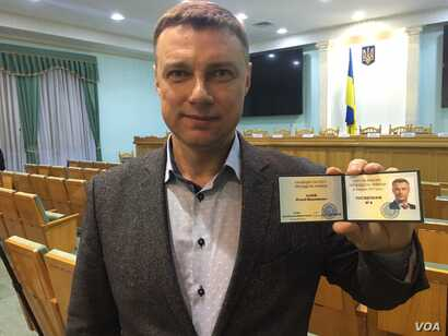 Member of parliament Vitaliy Kupriy holds up his registration as a candidate in Ukraine's upcoming presidential elections in an undated photo from his Facebook page.