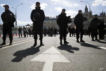 Police officers stay guard during an opposition rally in Moscow downtown, Russia, May 6, 2017. People gather for the rally against the Kremlin and demanding the release of political prisoners, five years since the opposition protest at May 6, 2012, t...