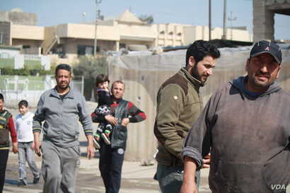 Mahmoud Abd (R) and his neighbors say they continue to be sickened by the smell from a nearby suspected chemical bomb and they still don't know exactly what was in it, in eastern Mosul, Iraq, March 8, 2017.