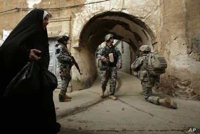 FILE -  an Iraqi woman passes U.S. troops and Iraqi police officers as they stand guard in the Bab al-Jadeed area of Mosul, 360 kilometers (225 miles) northwest of Baghdad, Iraq.