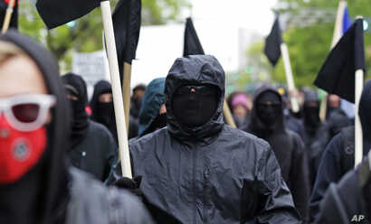 Black-clad protesters take part in a May Day march, May 1, 2015 in Seattle.