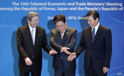 South Korea's Trade, Industry and Energy Minister Yoon Sang-jick, center, tries to hold hands to pose for the media with Japan's Economy, Trade and Industry Minister Motoo Hayashi, left, and China International Trade Representative Zhong Shan before ...