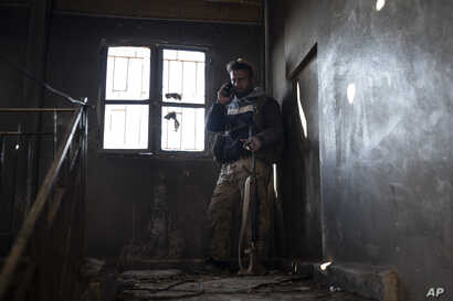 A U.S.-backed Syrian Democratic Forces fighter talks on his phone inside a building used as a temporary base near the last land still held by Islamic State militants in Baghouz, Syria, Feb. 18, 2019.