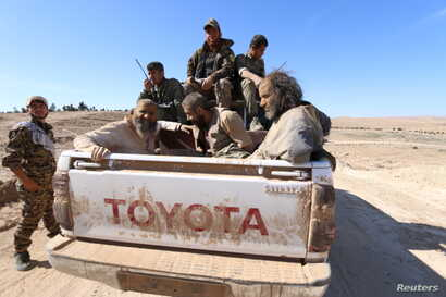 Islamic State fighters sit on a pickup truck while being held as prisoners by fighters of the Syrian Democratic Forces near Ash Shaddadi, Hasakah province, Syria, Feb. 18, 2016.