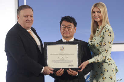 Kim Jong-chul, center, from South Korea, receives an award from Secretary of State Mike Pompeo, left, and Ivanka Trump, right, the daughter and assistant to President Donald Trump, during an event to announce the 2018 Trafficking in Persons Report in...