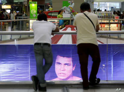 """Filipino fans look at the memorabilia of the Oct. 1, 1975 """"Thrilla in Manila"""" World Heavyweight boxing fight between Muhammad Ali and Joe Frazier at the launch of an exhibit at The Ali Mall in suburban Quezon city northeast of Manila, Philippines Fri..."""