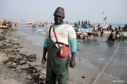 Doudou Kote, the captain of a Senegalese fishing vessel, stands on the beach at Joal-Fadiouth, a hub of the country's fishing industry, April 10, 2018.