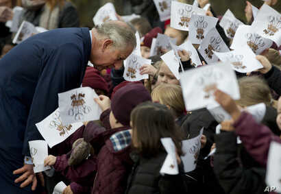 Schoolchildren wave images of the heraldic cypher of Britain's Prince Charles, as he bends down to talk to some of them, after he made a visit to meet Iraqi Christians in London,  Dec. 9, 2014.
