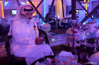 A Saudi man uses his smartphone as he smokes water pipe at a cafe in Dammam, Saudi Arabia, March 7, 2016.