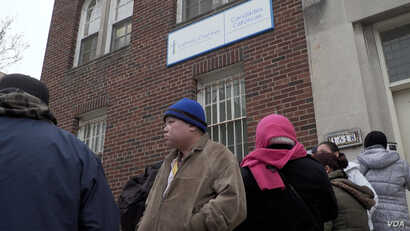 People wait in line for food assistance at the Catholic Charities center in Washington, D.C.'s Columbia Heights neighborhood. Many spoke openly of their fears of being deported.