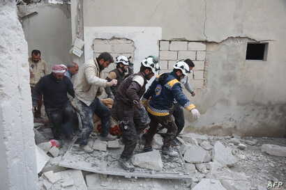 "Members of the Syrian Civil Defence (also known as ""The White Helmet"") carry a wounded person following reported shelling in the town of Khan Sheikhun in the southern countryside of the rebel-held Idlib province, Feb. 26, 2019."