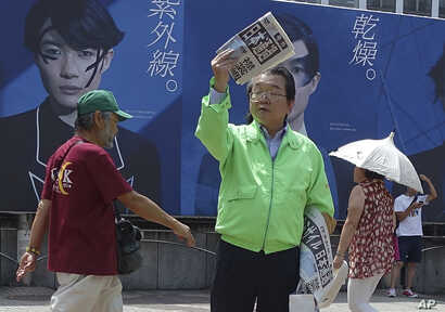 A staff of a Japanese newspaper hands out passer-by an extra edition reporting North Korea's rocket launch at a street corner  in Tokyo, Aug. 29, 2017.