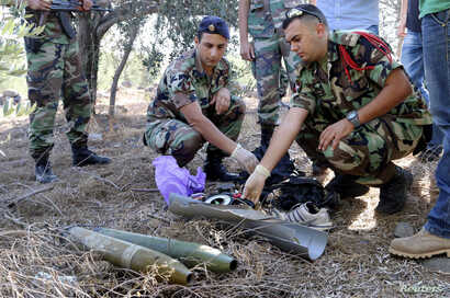 Lebanese army personnel inspect the remains of a shell suspected of having been launched from Lebanon to Israel, near the village of El Mari in southern Lebanon July 11, 2014.