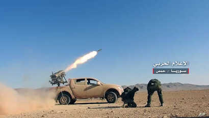 May 25, 2017 photo provided by the government-controlled Syrian Central Military Media, shows Syrian government troops firing multiple launcher rockets at insurgent group's position, in the Syrian province of Homs.
