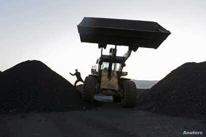 FILE : A driver gets off a loading vehicle at a small coal depot near a coal mine on the outskirts of Jixi, in Heilongjiang province, China, Oct.  23, 2015.