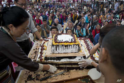Exile Tibetans wait for a cake to be distributed as they mark the 82nd birthday of their spiritual leader the Dalai Lama in Dharmsala, India, July 6, 2017. In a public event attended by hundreds, Tibetans danced, distributed sweets and offered their ...