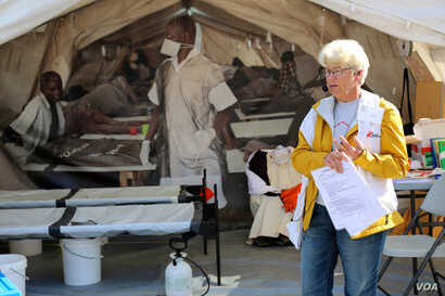 """Jane, a tour guide and former nurse with Médecins Sans Frontières, describes a typical medical tent at a refugee camp at the """"Forced From Home"""" display in Washington, D.C. (B. Allen/VOA)"""