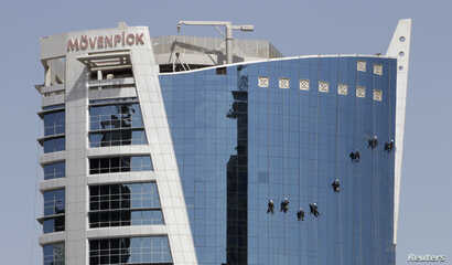 FILE - Cleaners wash the glass windows of the Movenpick Hotel in Doha, Qatar.