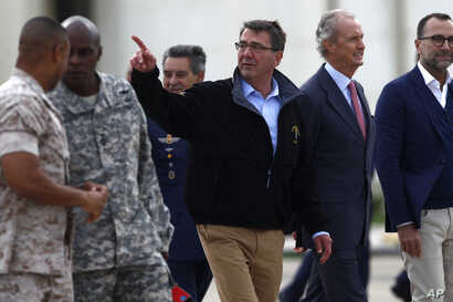 US Secretary of Defense Ashton Carter, center, and Spain's Defense Minister Pedro Morenes, right, walk together during their visit at Moron Airbase, near Seville, Spain, Oct. 6, 2015.