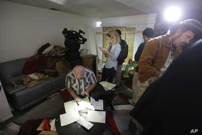 Reporters and photographers crowd into the living room of an apartment in Redlands, Calif., shared by San Bernardino shootings suspects Syed Farook and his wife, Tashfeen Malik, Dec. 4, 2015.