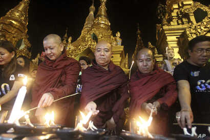 Buddhist monks light oil lamps during Earth Hour celebrations at Myanmar's Shwedagon pagoda in Yangon, March 25, 2017.