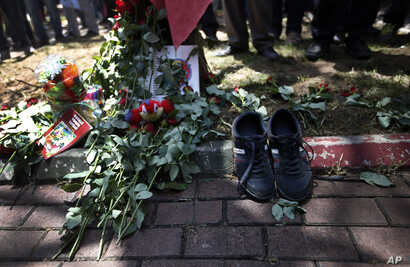 A pair of shoes belonging to a victim are seen next to flowers, laid down by mourners at the site of Monday's explosion in the Turkish town of Suruc near the Syrian border, Tuesday, July 21, 2015. Authorities suspected the Islamic State group was beh...