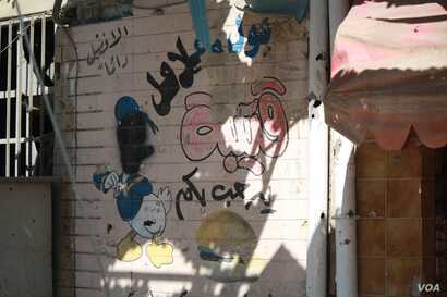 IS militants said images of faces were sinful and painted over pictures of even cartoon faces in Dawasa, western Mosul on March 10, 2017. (H. Murdock/VOA)