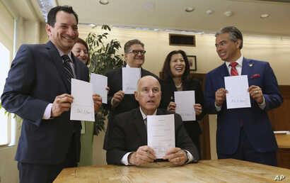 Governor Jerry Brown holds a copy of a bill to end bail that he signed in Sacramento, Calif., Aug. 28, 2018.