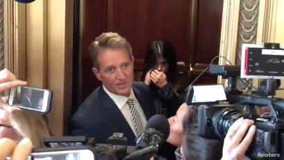 Senator Jeff Flake reacts during a confrontation with a protester in an elevator in Washington, D.C., Sept. 28, 2018 in this still image obtained from a social media video.