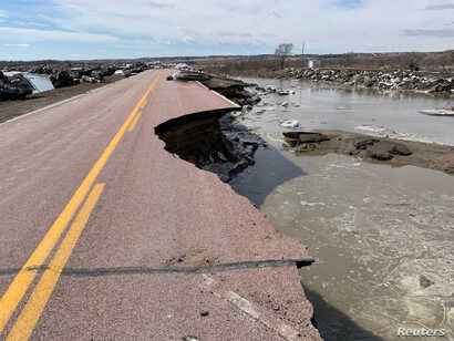 A damaged road is seen after a storm triggered historic flooding in Niobrara, Nebraska, March 16, 2019.