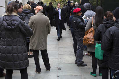 A voter walks between people waiting for their chance to cast their ballots at New York City Hall, November 6, 2012.