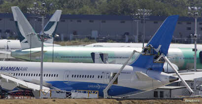FILE - Workers on lifts are pictured near the tail of a Boeing 787-8 Dreamliner being built for for Xiamen Airlines.