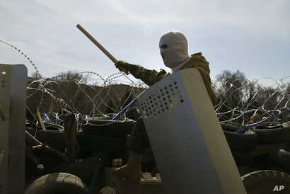 A masked man stands atop of a barricade at the regional administration building in in Donetsk, Ukraine, April 7, 2014.