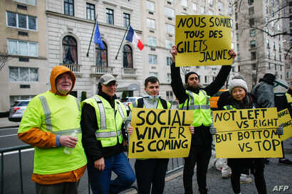 """People participate in a """"yellow vests"""" protest in front of the French Consulate in New York, Dec. 22, 2018."""