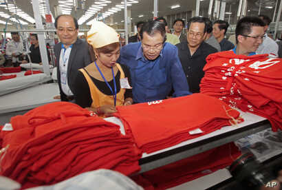 FILE - Prime Minister Hun Sen, center, leans over a garment worker during a visit to a factory outside Phnom Penh, Cambodia, Aug. 30, 2017.
