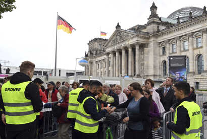 FILE - Visitors to the inaugural mass on the  lawn near the Reichstag being checked by security forces before their entry to the grounds in Berlin, Germany, May 24,  2017.