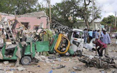 Somalis walk near destroyed vehicles at the scene of a car bomb blast and gun battle targeting a restaurant in Mogadishu,  June 15, 2017.