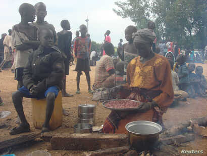 A displaced South Sudanese woman prepares a meal in a camp for internally displaced people in the UNMISS compound in Tomping, Juba, South Sudan, July 12, 2016.