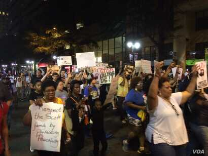 """Protesters, marching for a fourth night after an African-American man was shot to death by police on Tuesday, chant, """"Hands up, don't shoot,"""" as they walk, in Charlotte, North Carolina, Sept. 23, 2016."""