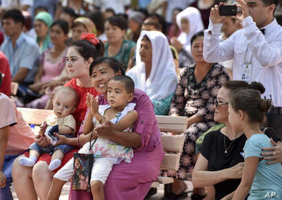 Uzbeks watch a performance at a park in downtown Tashkent, Uzbekistan, during Independence Day festivities, Sept. 1, 2016.